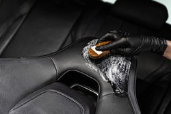 Man in rubber gloves cleaning leather car seat