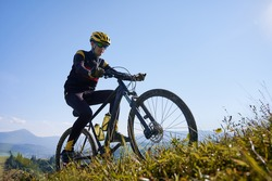 Man in safety helmet and glasses cycling uphill on sunny day with blue sky on background. Male bicyclist in cycling suit climbing uphill on mountain bike. Concept of sport and active leisure.