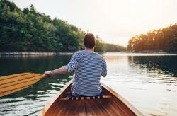 Man in sailor shirt paddling canoe on the sunset lake