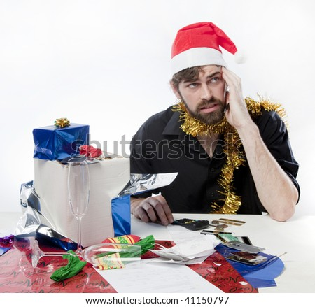 Man in Santa Claus hat looking depressed about his finances