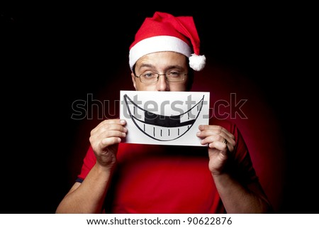 Man in Santa Hat holding a hand drawn smile up to his face, with front teeth missing, and his eye-brow cocked ironically.