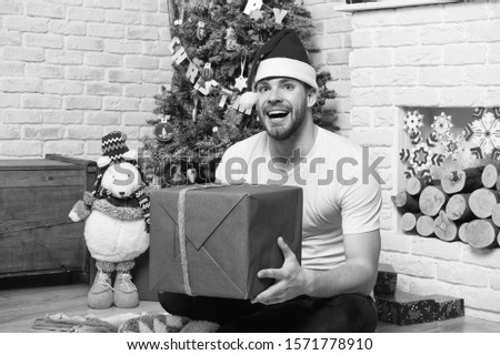Man in santa hat sit on floor at fireplace. Macho smile with present box, toy bear at xmas tree. Boxing day concept. Christmas and new year presents preparation. Happy holidays celebration.