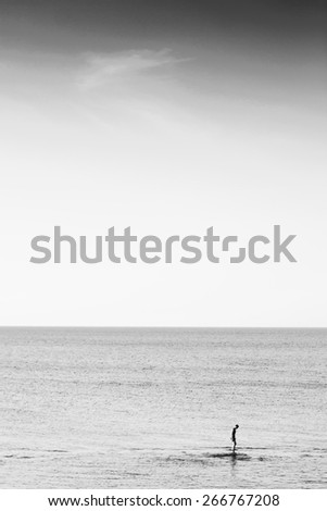 Man in sea. Man stands on water in open sea. Black and white photo