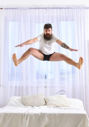 Man in shirt and underpants jumping on bed, white curtains on background. Macho with beard jumps high in air. Guy on cheerful face full of energy in morning. Full of strength and energy concept