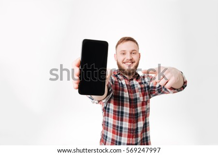 Man in shirt showing blank smartphone screen and pointing at phone. Isolated white background #569247997