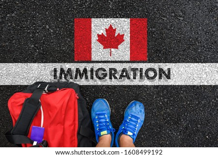 Man in shoes with bag standing next to line with word IMMIGRATION and flag of Canada on asphalt road Сток-фото ©