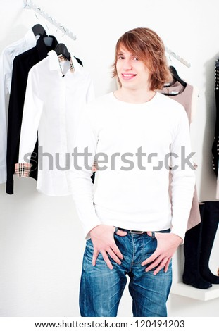 man in shop of clothes, smiles and is happy with purchases