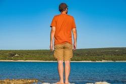Man in short cargo pants observing the sea surface, Losinj island, Croatia