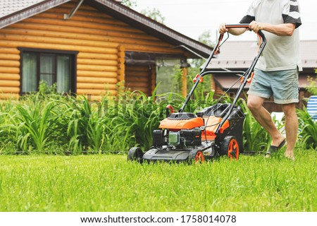 Man in shorts mowing the grass on the lawn. Young man cutting grass in his yard with lawn mower. Gardener mowing the lawn with lawnmower in summertime - closeup.