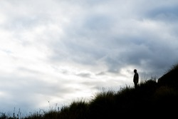 Man in silhouette on hill with cloudy sky background