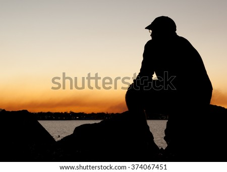 Man in silhouette sitting contemplating watching sunset