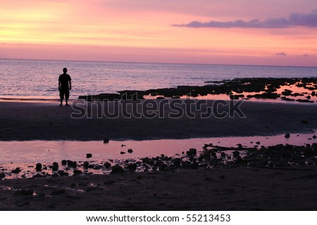 Man in silhouette standing on beach in colorful pink sunset