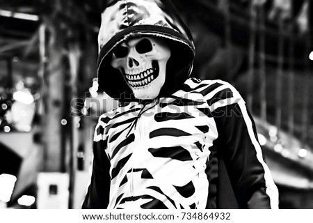 Stock Photo Man in skeleton costume on the walking street in Thailand. This image was blurred or selective focus. Black and white picture.
