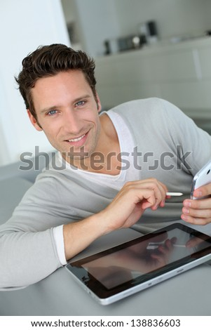 Man in sofa using tablet and smartphone