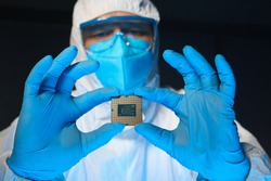 Man in special uniform shows microprocessor chip. Software-controlled device for processing information. Production technology. Development special chip. Scientist is engaged in chip implementation
