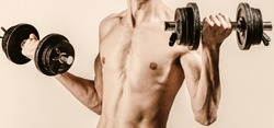 Man in sports with dumbbells. Weak man lift a weight, dumbbells, biceps, muscle, fitness. Nerd maleraising a dumbbell. Man holding dumbbell in hand. Skinny guy hold dumbbells up in hands.
