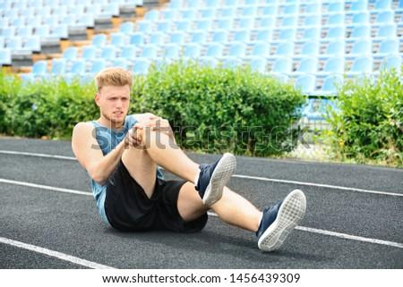 Man in sportswear suffering from knee pain at stadium