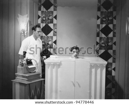 Man in steam bath with assistant and dictaphone