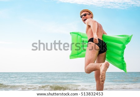 Man in straw hat runs with air swimimg mattress in the sea #513832453