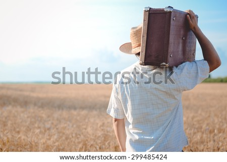 Man in straw hat with a retro suitcase on his shoulder