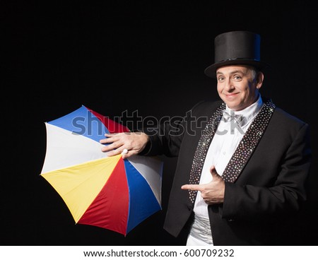 Man in suit and hat introduce color umbrella isolated on black background  Stock fotó ©