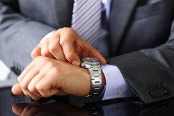Man in suit and tie check out time at silver wristwatch closeup. Waste minute, modern punctual life style, start hurry, job idea, last second, clockwork precision concept