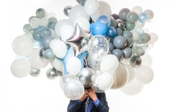Man in suit covering face with bunch of helium balloons. Businessman hides head in air balloons. Guy with many air balloons. Birthday, New Year party, holidays. Balloons background. Wedding decoration