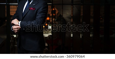 Shutterstock Man in suit fixing his cufflinks