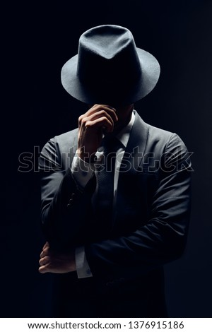 Man in suit hiding face behind his hat isolated on dark background. secret and incognito concept