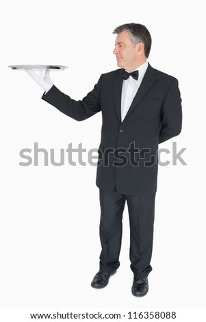 Man in suit holding empty silver tray