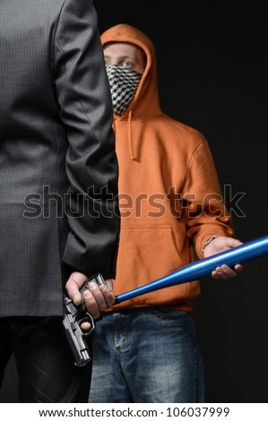 Man in suit holding gun behind his back, in front of him man with baseball bat