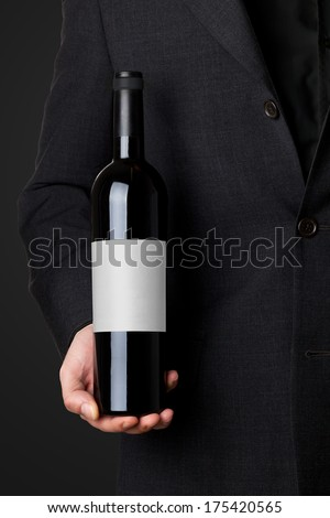 Man in suit holding red wine bottle isolated on black background