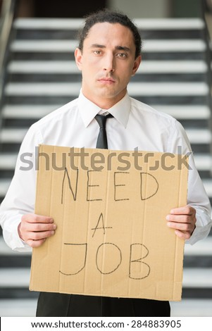 Man in suit holding sign in hands. Unemployed man looking for job.