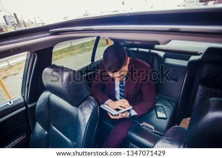 Man in suit is driving in a stretch limo and taking notes in his notebook getting ready before a meeting
