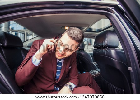 Man in suit is going to a meeting while driving in a limo getting ready before a meeting