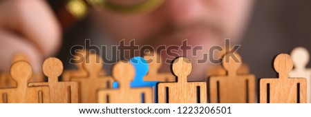 Man in suit look thru loupe on statuettes closeup in office. Success hr assessment people headhunt inspector applicant exchange 404 web error concept