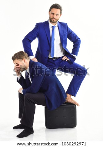 Man in suit or businessman sit on briefcase with desperate expression near confident colleague, isolated on white background. Leader and subordinate concept. Boss stand near subordinated employee.
