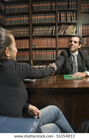 Man in suit sits behind desk. He shakes hand of woman on other side. Vertically framed photo.