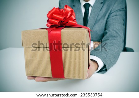 man in suit sitting in his office holding a gift with a red ribbon