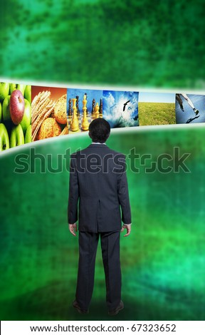 man in suit standing in front of screens with images