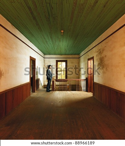 man in suit surveys the interior of an abandoned home