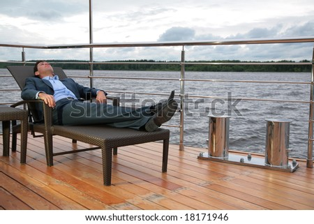 man in suit, who rests in chaise lounge on  wharf near water - stock photo