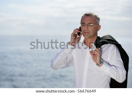 Man in suit with a mobile phone near the sea