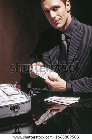 Man in suit with briefcase full of US Dollars