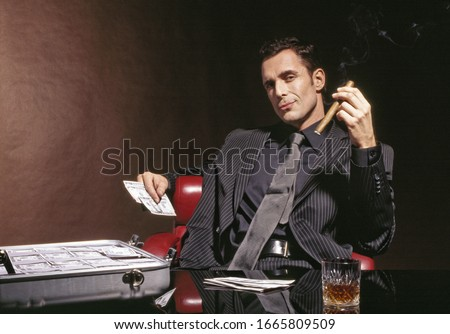 Man in suit with cigar and briefcase full of US Dollars
