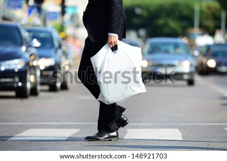 Man in suit with plastic bag crossing street #148921703
