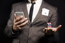 Man in suit with to aces in pocket holding poker chips and smartphone/ online poker