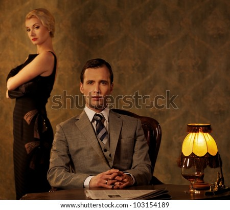 Man in suit  with woman behind him.