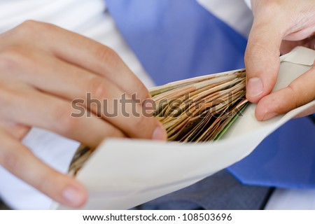 Man in suits is counting how much money in an envelope #108503696