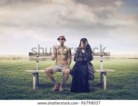 Man in summer clothes sitting on a park bench with woman wrapped in warm clothes beside him